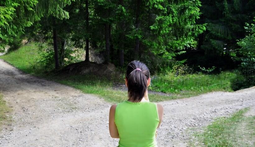 Eine Frau steht an einer Weggabelung